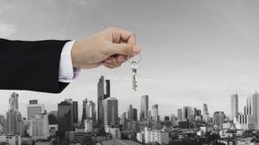 Ręki mienia klucze z Bangkok miasta tłem, kupienie domem, nieruchomością i domu wynajem pojęciami, Zdjęcie Stock