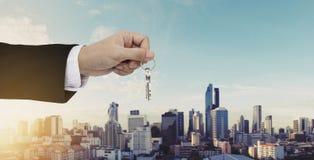 Ręki mienia klucze z Bangkok miasta tłem, kupienie domem, nieruchomością i domu wynajem pojęciem, Zdjęcie Stock