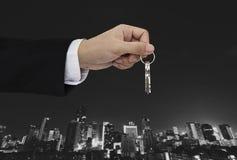 Ręki mienia klucze z miasta tłem, nieruchomością i własności pojęciem, Zdjęcia Stock