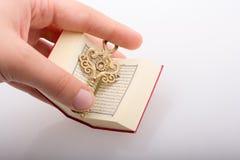 Ręki mienia Kluczowy i Islamski święta księga koran Zdjęcia Royalty Free