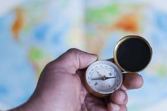 Ręki mienia kompas przed światową mapą Fotografia Stock