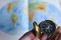 Ręki mienia kompas przed światową mapą Zdjęcie Stock