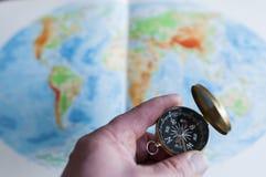 Ręki mienia kompas przed światową mapą Zdjęcia Royalty Free