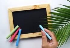 Ręki mienia kreda Pusty Drewnianej ramy Blackboard z Kolorowym zdjęcie royalty free