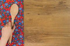 Ręki mienia kuchenna drewniana łyżka Deseniowego kwiatu sukienna pielucha dalej Fotografia Royalty Free