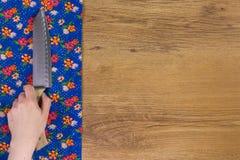 Ręki mienia kuchenny drewniany nóż Deseniowego kwiatu sukienna pielucha dalej Fotografia Royalty Free