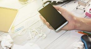 Ręki mienia męski smartphone na białym drewnianym biuro stole z b Fotografia Royalty Free