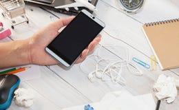 Ręki mienia męski smartphone na białym drewnianym biuro stole z b Zdjęcia Royalty Free