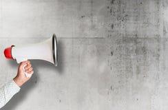 R?ki mienia megafon przeciw szorstkiej betonowej ?cianie zdjęcia stock