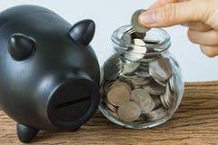 Ręki mienia moneta stawiać w słoju i czarnym prosiątko banku jako financia Zdjęcie Stock