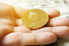 Ręki mienia monety ethereum ETH pod dolarowymi banknotami Cryptocurrency kopalnictwo obraz royalty free