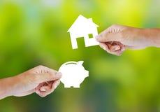 Ręki mienia papieru prosiątka dom i bank kształtujemy Obrazy Stock