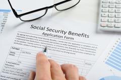 Ręki mienia pióro nad ubezpieczenie społeczne korzyści formą Zdjęcia Stock