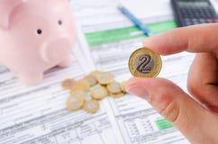 Ręki mienia połysku moneta Polskie podatek formy w tle Zdjęcie Stock