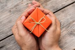 Ręki mienia prezenta Pomarańczowy pudełko i koloru żółtego faborek Zdjęcia Royalty Free