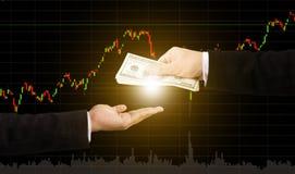 Ręki mienia przelew pieniędzy z wykresu rynkiem papierów wartościowych zamazywał z powrotem Obraz Royalty Free