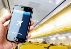 Ręki mienia smartphone wśrodku samolotu Zdjęcie Stock
