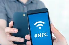 Ręki mienia smartphone z NFC technologią Zdjęcia Stock