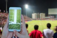 Ręki mienia smartphone z piłka nożna ekranem w stadionu futbolowego b Obraz Stock