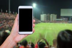 Ręki mienia smartphone z piłka nożna ekranem w stadionu futbolowego b Obraz Royalty Free