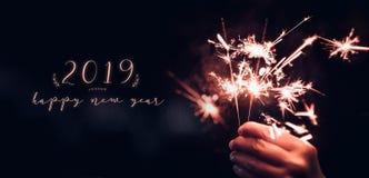 Ręki mienia Sparkler płonący wybuch z szczęśliwym nowym rokiem 2019 dalej fotografia royalty free