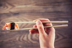 Ręki mienia suszi rolka używać chopsticks Zdjęcie Stock