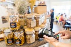 Ręki mienia telefon komórkowy na sklep z kawą Obrazy Stock