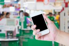 Ręki mienia telefon komórkowy przy supermarket kasy tłem Fotografia Royalty Free