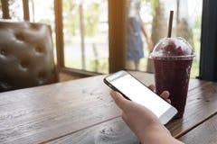 Ręki mienia telefon komórkowy w sklep z kawą egzaminie próbnym up na ekranie zdjęcia stock