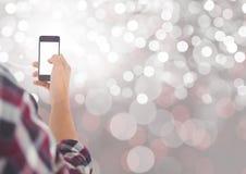 Ręki mienia telefon komórkowy z lśnienia światła bokeh tłem Zdjęcia Royalty Free
