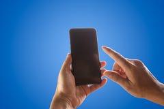 Ręki mienia telefonu wisząca ozdoba i macanie ekran odizolowywający na błękicie zdjęcie royalty free