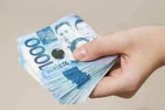 Ręki mienie składał plika błękitny pieniądze w gotówce tysiąc Filipiny peso Dawać łapówce, płacący rachunki lub dostawać pensję P zdjęcia stock