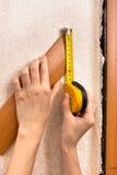 Ręki mierzy szerokość platband z taśmy miarą fotografia stock