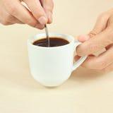 Ręki miesza z łyżką czarna kawa w filiżance Obrazy Royalty Free