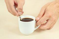 Ręki miesza z łyżką gorąca kawa w filiżance Fotografia Royalty Free