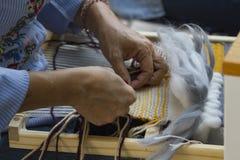 Ręki na Pionowo makacie z beżową koloru żółtego i błękita nicią zdjęcie royalty free