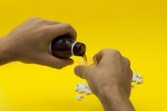 Ręki nalewa medycznego syrop w pomiarowej filiżance Obraz Stock