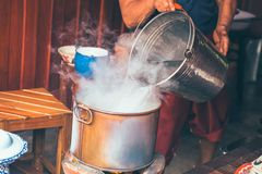 Ręki nalewają wodę w garnku dla czyraka Czyrak woda dla jedzenia zdjęcie stock