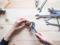 Ręki, narzędziowego i dużego orzech włoski na drewnianym tle, Pojęcie powikłani problemy wyzwanie może rozwiązujący obraz stock