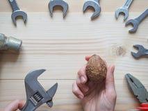 Ręki, narzędziowego i dużego orzech włoski na drewnianym tle, Pojęcie powikłani problemy wyzwanie może rozwiązujący obrazy stock