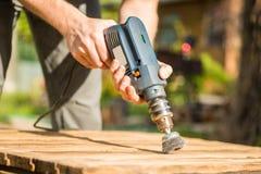 Ręki obsługują z elektrycznym płodozmiennym szczotkarskim metalu dyskiem sanding kawałek drewno Obraz Stock