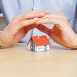 Ręki ochrania małego dom Zdjęcia Stock