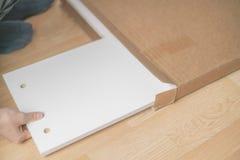 Ręki odpakowania łęk z nowym meble na drewniany podłogowy b zdjęcie stock