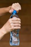 Ręki otwiera butelkę z wodą Fotografia Stock