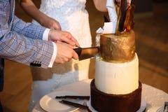 Ręki państwo młodzi cią wielopoziomowego słodkiego ślubnego tort białego złota kolor Stół z cukierkami, cukierku bar obraz stock