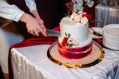 Ręki państwo młodzi cią wielopoziomowego słodkiego ślubnego tort dekorującego z kwiatami Stół z cukierkami, cukierku bar obrazy royalty free