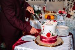 Ręki państwo młodzi cią wielopoziomowego słodkiego ślubnego tort dekorującego z kwiatami Stół z cukierkami, cukierku bar zdjęcie royalty free