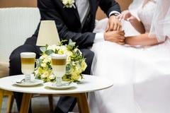 Ręki państwo młodzi dla filiżanki kawy Ślubny bukiet na stole Zdjęcia Royalty Free
