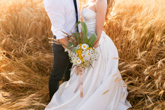 Ręki państwo młodzi nad pszenicznym polem Bajki romantyczna para nowożeńcy ściska przy zmierzchem zdjęcie stock