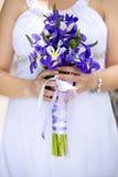 Ręki panny młodej mienia ślubny bukiet fiołkowi i biali kwiaty Zdjęcia Stock